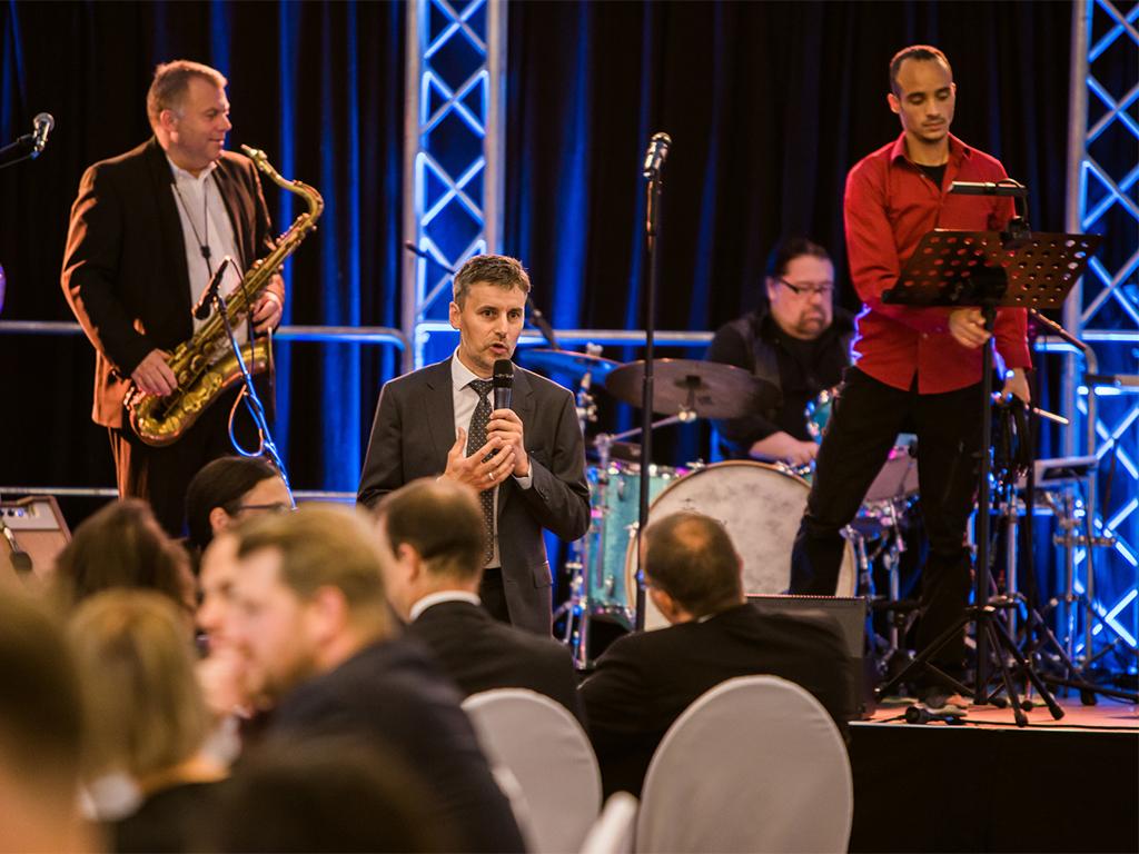 Stefan Dietz als Moderator bei einer Gala eines Verbandes. Musikalische Umrahmung im Hintergrund, festlich dekorierte Tische im Vordergrund.